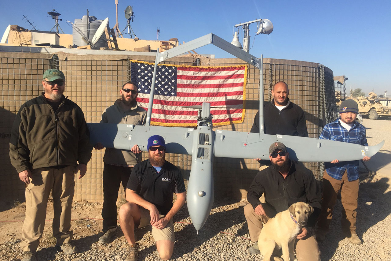 Six men posing around a drone. The drone is being held up in front of an American Flag